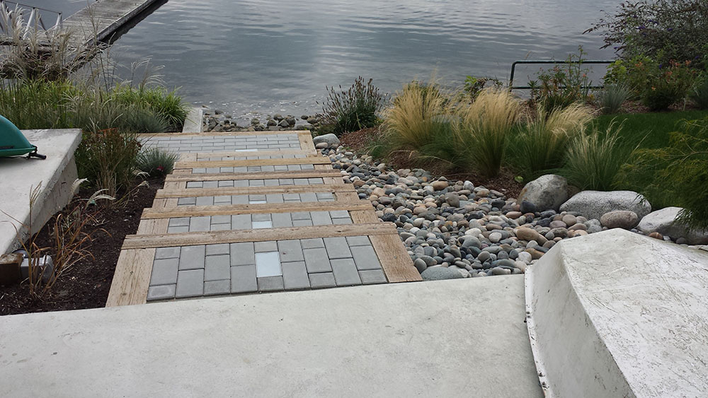 Landscape Installation Serivce including paving stone pathway bordered by wood and river rocks leading to the ocean