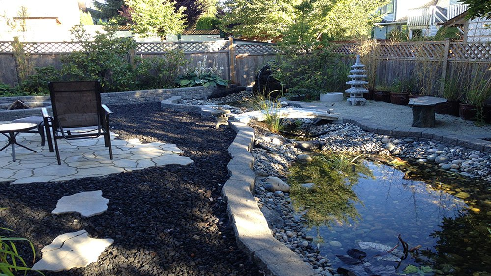 Vancouver Landscape Installation Service including flagstone patio surrounded by black lava rock and pond with water feature