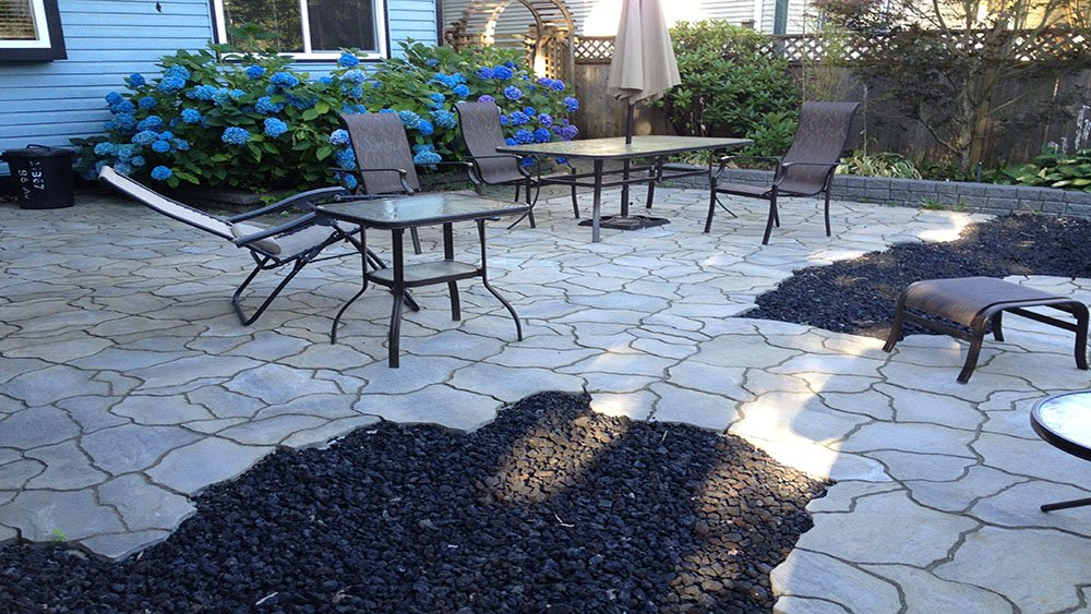 Coastal pacific landscaping Service including flagstone patio surrounded by black lava rock with hydrangeas in the background