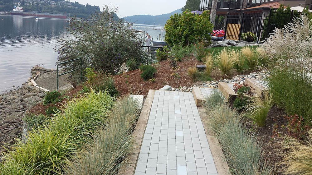Landscape Installation Service including paving stone pathway bordered by grasses over looking the ocean